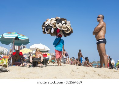 RIO DE JANEIRO, BRAZIL - MARCH 05, 2013: Brazilian beach vendor selling hats walks with merchandise among sunbathers on Ipanema Beach.