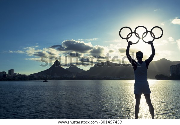 RIO DE JANEIRO, BRAZIL - MARCH 05, 2015: man holding Olympic rings above sunset city skyline view of Two Brothers Mountain at Lagoa de Freitas Lagoon.