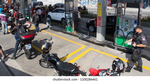 RIO DE JANEIRO, Brazil   May, 27th, 2018  Drivers truck strike An anti- riot police agent guards a gas station as Rio's resident motorbikers stay on line to fuel due the gasoline shortage