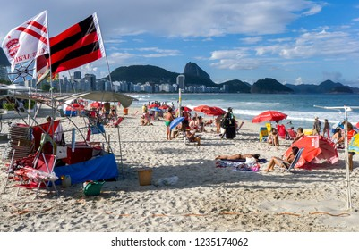 RIO DE JANEIRO, BRAZIL - MAY 07, 2012 : Late afternoon sunbathers relax on Copacabana Beach in Rio de Janeiro. In the background is the famous Sugarloaf Mountain.