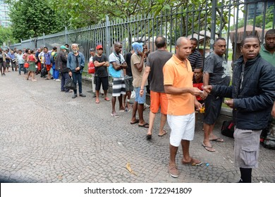 RIO DE JANEIRO (BRAZIL), MAY 05,2020 Homeless people line up to receive lunch at the Largo da Carioca in downtown Rio de Janeiro and a group of volunteers gather to distribute the hot dogs in times o