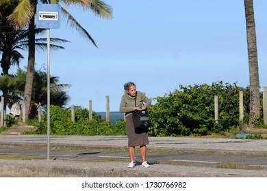 Rio de Janeiro, Brazil, May 11, 2020. Elderly woman waiting for a bus at Av Lucio Costa stop on Barra da Tijuca beach.
