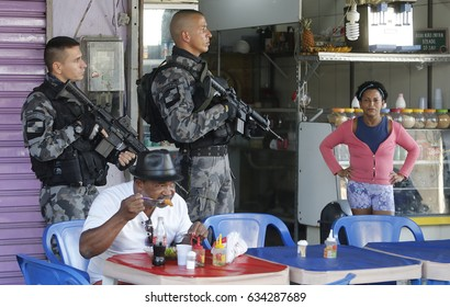 RIO DE JANEIRO, Brazil May, 04th,2017 A inhabitant at Alemao shantytown  have a lunch at a local bar as Anti- riot policemen secures the place after a confrontation with drug lords.