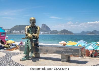 Rio de Janeiro, Brazil - Nov 2, 2017: Carlos Drummond de Andrade Statue at Copacabana Beach with Sugar Loaf Mountain on background - Rio de Janeiro, Brazil