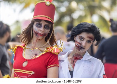 Rio de Janeiro, Brazil - November 2, 2019: Halloween walk of zombies on the Day of the Dead, Finados, on Copacabana boulevard with a female fanfare and nurse zombie with palm trees in the background