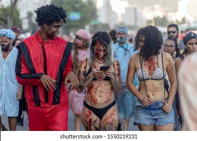 Rio de Janeiro, Brazil - November 2, 2019: Halloween walk of zombies on the Day of the Dead, Finados, in Copacabana with an undead Michael Jackson in thriller outfit and zombie groupies in bikini