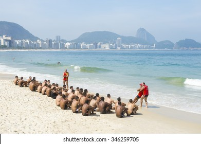 RIO DE JANEIRO, BRAZIL - NOVEMBER 10, 2015: Training for the city's Guarda-Vidas (lifeguards) involves a rigorous test of stretching and physical endurance on Copacabana Beach.