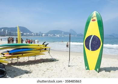 RIO DE JANEIRO, BRAZIL - NOVEMBER 10, 2015: Brazilian flag surfboard stands in front of a lifeguard training course on Copacabana Beach.