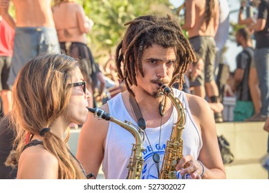 RIO DE JANEIRO, BRAZIL - NOVEMBER 27, 2016: Woman and man with dreadlocks playing saxophones at sunny day at Festival Fanfare Activist Festival de Fanfarras Ativistas - HONK RiO 2016 at Leme district