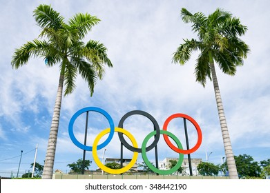 RIO DE JANEIRO, BRAZIL - OCTOBER 31, 2015: Olympic rings stand under tall palm trees in a city park.