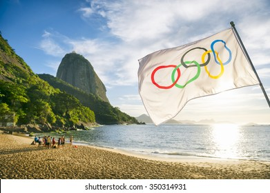 RIO DE JANEIRO, BRAZIL - OCTOBER 31, 2015: Olympic flag waves in front of the rising sun at Red Beach in anticipation of the 2016 Summer Games.
