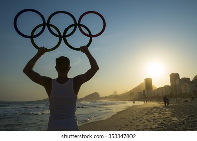 RIO DE JANEIRO, BRAZIL - OCTOBER 30, 2015: Athlete holds Olympic rings above sunset city skyline view of Copacabana Beach at Leme.