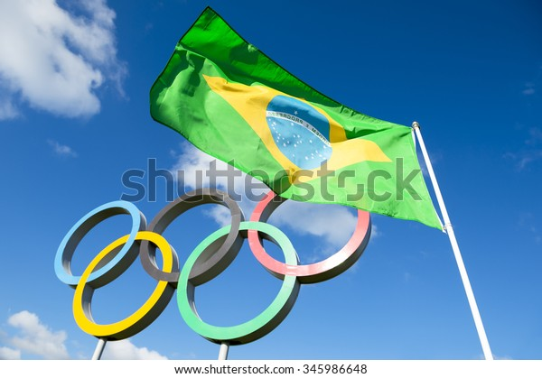 Rio de Janeiro, Brazil  - OCTOBER 14, 2015: Brazilian flag flies next to the Olympic rings standing under bright blue sky in the Queen Elizabeth Olympic Park. [illustrative editorial]