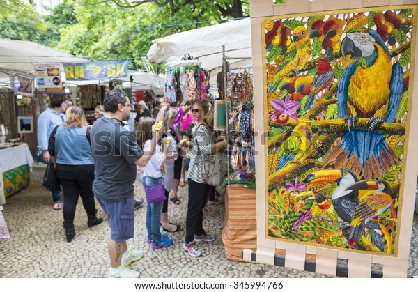 RIO DE JANEIRO, BRAZIL - OCTOBER 25, 2015: Shoppers look at art displayed at the outdoor Hippie Fair market in General Osorio Plaza in Ipanema.