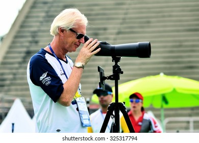 RIO DE JANEIRO, BRAZIL: SEPTEMBER 20, 2015: Colombian coach uses a scope to see his team's arrows during the practice for the Archery competition as part of AqueceRio test event for the 2016 Olympics.