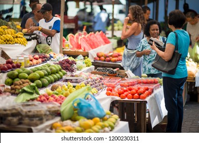 RIO DE JANEIRO - CIRCA FEBRUARY, 2018: Vendors tend to customers at the weekly tropical fruit market in Ipanema.