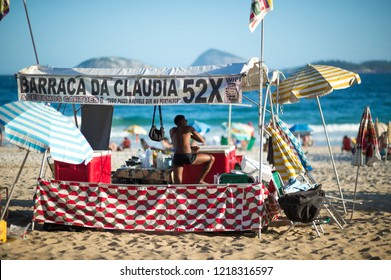 RIO DE JANEIRO - CIRCA FEBRUARY, 2018: A young man minds a beach shack, one of the many serving drinks, chairs, and umbrellas to beachgoers on Ipanema Beach.