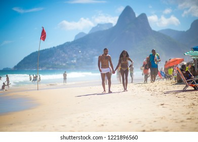 RIO DE JANEIRO - CIRCA FEBRUARY, 2018: A young Brazilian couple hold hands as they walk past a red flag standing above dangerous waves crashing on the shore.