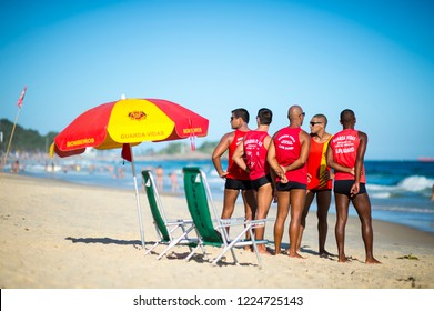 RIO DE JANEIRO - CIRCA FEBRUARY, 2018: A group of lifeguards stand together in uniform on Ipanema Beach, where rough waves demand strong swimmers who undergo rigorous training for the job.