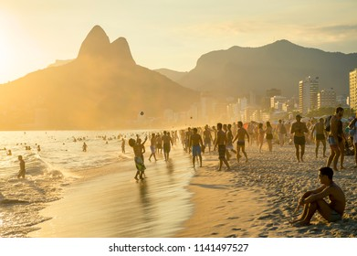 RIO DE JANEIRO - CIRCA JANUARY, 2014: Beachgoers on Ipanema Beach sit back to take in the sunset behind Two Brothers Mountain.