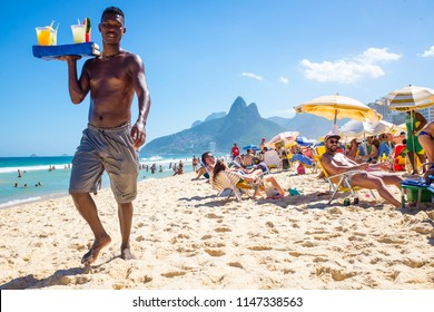 RIO DE JANEIRO - CIRCA MARCH, 2018: A beach vendor selling caipirinhas calls out to potential customers on Ipanema Beach with Two Brothers mountain backdrop.