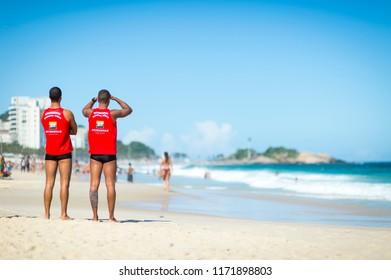 RIO DE JANEIRO - CIRCA MARCH, 2018: Pair of athletic Brazilian lifeguards in uniform watch the heavy surf on Ipanema beach. TRANSLATION 'Bombeiros Guarda Vidas' - Firemen Life Guards.