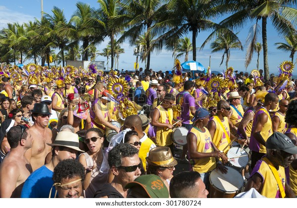 RIO DE JANEIRO - FEBRUARY 07, 2015: Brazilians celebrate at a carnival street party on a sunny summer afternoon along Ipanema Beach.
