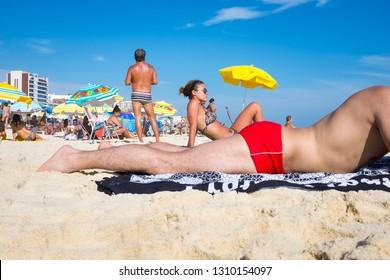 RIO DE JANEIRO - FEBRUARY 08, 2015: Beachgoers relax on a bright summer day in Ipanema Beach.