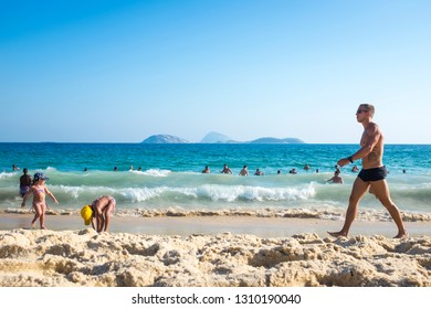 RIO DE JANEIRO - FEBRUARY 08, 2015: A young Brazilian man wearing sunga, a popular local style of swimwear, walks along the shore of Ipanema Beach.