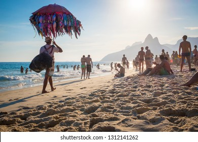 RIO DE JANEIRO - FEBRUARY 08, 2015:  A Brazilian vendor selling bikinis carries his merchandise hanging from an umbrella past potential buyers on Ipanema Beach.