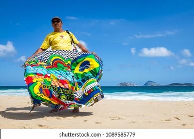 RIO DE JANEIRO - FEBRUARY 10, 2017: A Brazilian vendor selling colorful canga (sarong) souvenirs walks on Ipanema Beach.