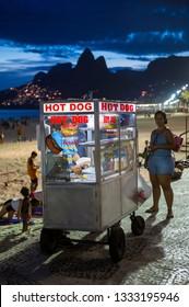 RIO DE JANEIRO - FEBRUARY 10, 2017: A customer stands waiting as a vendor prepares her order at a mobile hot dog cart on the Ipanema Beach boardwalk at Arpoador.