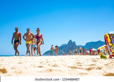 "RIO DE JANEIRO - FEBRUARY 10, 2017: Young Brazilian men wearing a style of swimwear known locally as ""sunga"" walk with a woman in a bikini on the shore of Ipanema Beach."