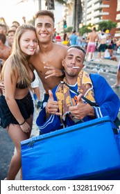 RIO DE JANEIRO - FEBRUARY 11, 2017: A Brazilian street vendor photobombs a picture at an afternoon Carnival street party on the Ipanema beachfront.