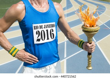 RIO DE JANEIRO - FEBRUARY 12, 2016: Athlete wearing 2016 race bib holds sport torch in front of running track in celebration of the city hosting the Summer Games.