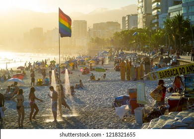 RIO DE JANEIRO - FEBRUARY, 2018: Young people shower under a gay pride rainbow flag as the sun sets above Ipanema Beach, a neighborhood known for its tolerance and support of lgbtq rights.