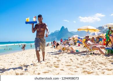 RIO DE JANEIRO - FEBRUARY, 2018: An unlicensed Brazilian beach vendor carries a tray of homemade caipirinha cocktails past beachgoers on Ipanema Beach.