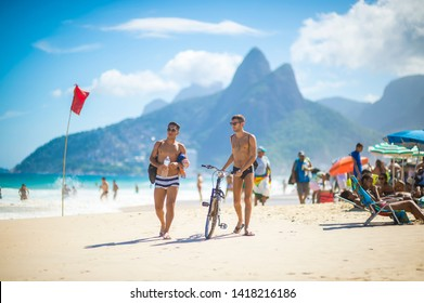 RIO DE JANEIRO - FEBRUARY, 2018: A pair of young Brazilian men walk with a bicycle past sunbathers on Ipanema Beach.