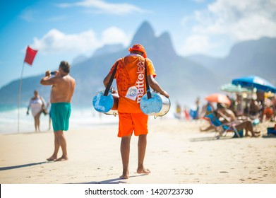 RIO DE JANEIRO -  FEBRUARY, 2018: A young Brazilian vendor selling cold mate, the South American tea, walks past tourists relaxing in chairs on Ipanema Beach.