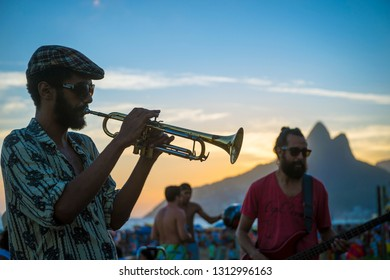 RIO DE JANEIRO - FEBRUARY 21, 2015: Young Brazilian musicians play Bossa Nova jazz music in an informal performance on the Ipanema Beach boardwalk as the sun sets at Arpoador, the popular view point.