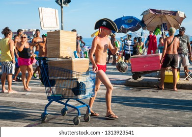 RIO DE JANEIRO - FEBRUARY 28, 2017: A Brazilian street vendor pulls a shopping cart with coolers of beer to sell to crowds of young people celebrating at an afternoon Carnival street party in Ipanema.