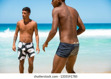 RIO DE JANEIRO - FEBRUARY 5, 2017: A pair of young Brazilian men get ready to kick the ball in a round of altinho, the ubiquitous game of keepy-uppy, on Ipanema Beach.