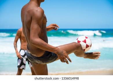 RIO DE JANEIRO - FEBRUARY 5, 2017: A pair of young Brazilian men kick a soccer ball playing altinho, the ubiquitous game of keepy-uppy, at the Arpoador surf break on Ipanema Beach.