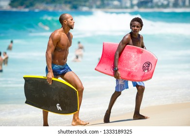 RIO DE JANEIRO - FEBRUARY 6, 2017: Young Brazilian surfers and bodyboarders gather on a bright summer afternoon at Arpoador, the popular surf break.