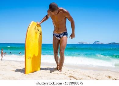 RIO DE JANEIRO - FEBRUARY 6, 2017: A young Brazilian body boarder stands with his board on the shore of Ipanema Beach