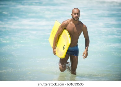 RIO DE JANEIRO - FEBRUARY 6, 2017: A handsome young Brazilian body boarder walks with his board through the waves at Arpoador, the popular surf break.