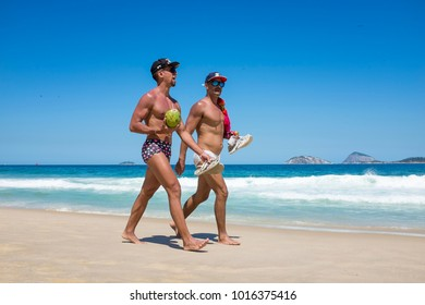 RIO DE JANEIRO - JANUARY 15, 2017: A pair of men in colorful swimwear walk with fresh coconut water and beer on the shore of Ipanema Beach.