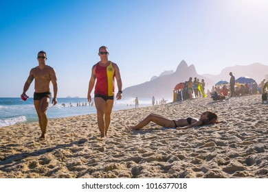 RIO DE JANEIRO - JANUARY 15, 2017: A pair of lifeguards pass sunbathers on a walking patrol along Ipanema Beach.