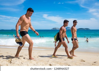 RIO DE JANEIRO - JANUARY, 2017: Young Brazilian men walk on Ipanema Beach wearing sungas, a style of swimming trunks popular with locals, usually worn under longer board shorts off the beach.