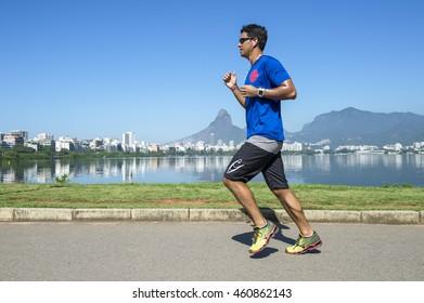 RIO DE JANEIRO - JANUARY 31, 2016: Jogger runs past a calm morning view of Lagoa Rodrigo de Freitas lagoon, a venue for the 2016 Summer Olympics.